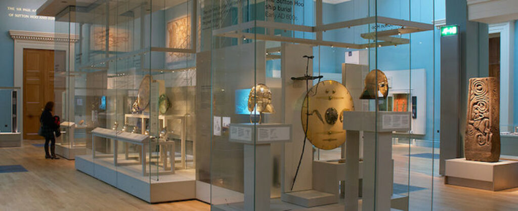 Die Helme, Schilde und weitere Schätze aus Sutton Hoo sind in Glasvitrinen in dem British Museum ausgestellt.
