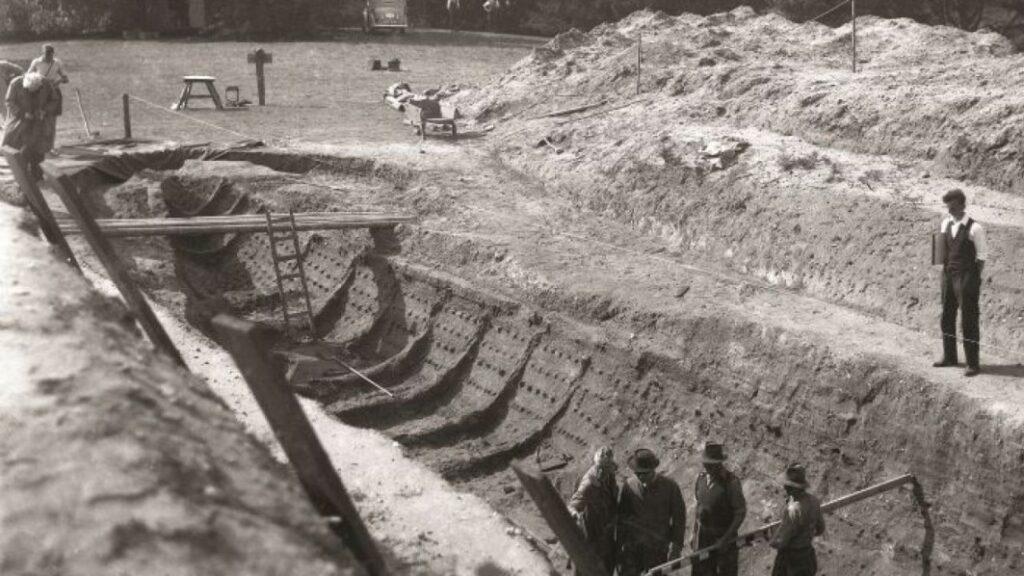 Das Schwarz-Weiß Bild zeigt das noch bis zum Rand in der Erde liegende Schiff, in dem die Ausgräber gespannt auf die Holzplanken blicken.