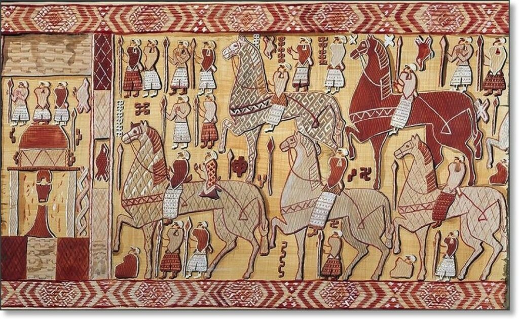 Der Teppich in rot-,, weiß- und hellbraun-Tönen zeigt mehrere Reiter auf großen Pferden und Krieger mit Speeren, die ihren Blick auf die linke Seite des Abbildes richten.