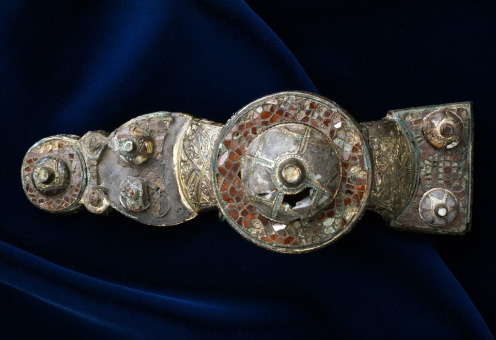 Fotografie einer Fibel mit geometrischen Elementen und Einlagen aus roten Steinen. Die Fibel stammt aus dem gleichen Grab, in dem auch der Reliquienschrein gefunden worden war.
