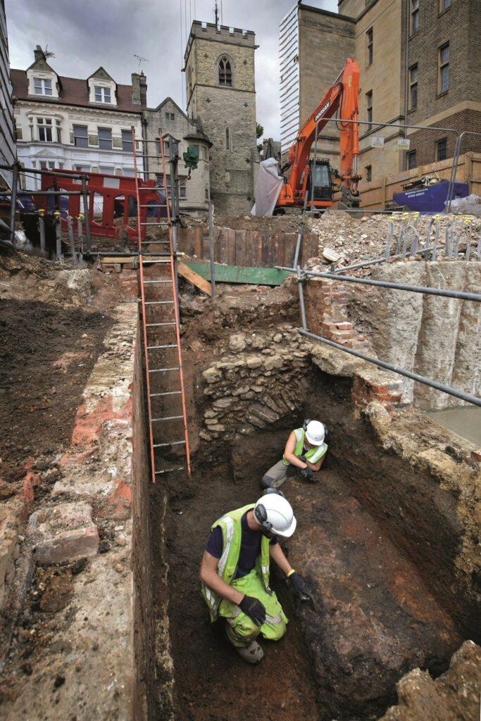 Fotografie: Ausgrabungen in Oxford (jüdische Viertel). Zwei Mitarbeiter knieen in einem Grabungsschnitt und untersuchen den Befund.