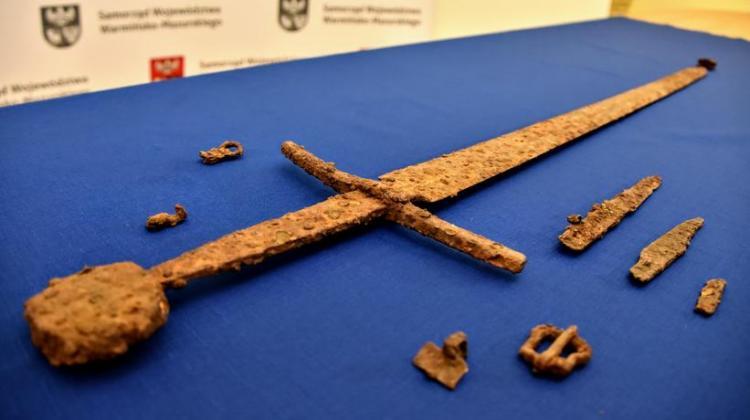 Die Funde des Hobbyarchäologen. Zu sehen sind Schwert, Elemente eines Gürtels und zwei Messer.