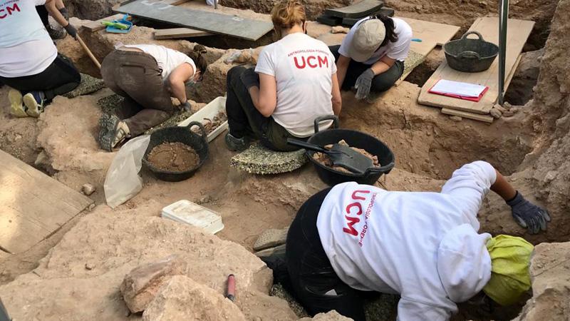 Mitarbeiterinnen und Mitarbeiter der UCM während der Bergungen der Leichen. Die Beteiligten sitzen zwischen den Grabungsschnitten/Gruben und legen die Überreste der Bestatteten frei.
