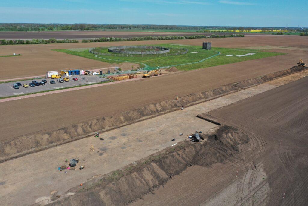 Das Luftbild zeigt die großflächige Grabungsfläche, die untersucht wird. Im Hintergrund ist das Ringheiligtum von Pömmelte, umgeben von Äckern, zu sehen.