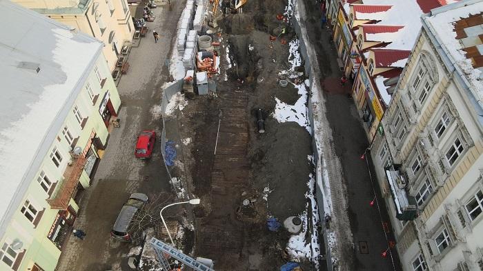 Luftbildaufnahme der freigelegten Holzstraße während der Ausgrabungen. Die Straße befindet sich direkt in der Stadt unterhalb der modernen Straße. Die Holzbalken sind teilweise noch von der dunklen Erde bedeckt. Am Rand der Grabungsfläche liegt Schnee. Flankiert wird die Grabung von einer Häuserreihe zu beiden Seiten.