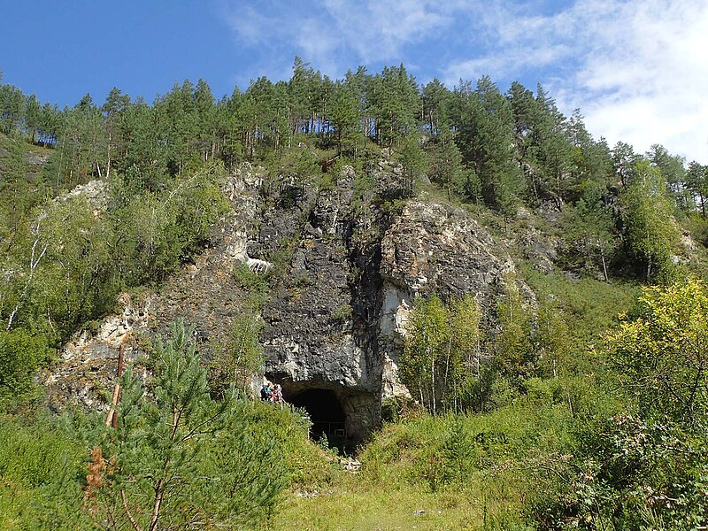 Fotografie der Denisova-Höhle aus der die analysierte DNA stammt.  Die Höhle ist ebenerdig begehbar und befindet sich am Fuße eines hohen Berges und wird von einem Mischwald umringt.