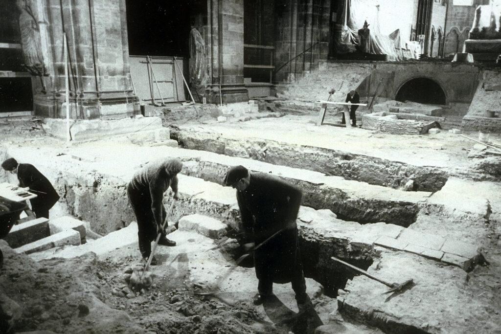 Schwarz-weiß Foto der Ausgrabungen im Heinrichsdom. Zu sehen ist ein Teil des Mittelschiffs sowie drei Personen, von denen zwei Erde mit Hilfe von Schaufeln entfernen.