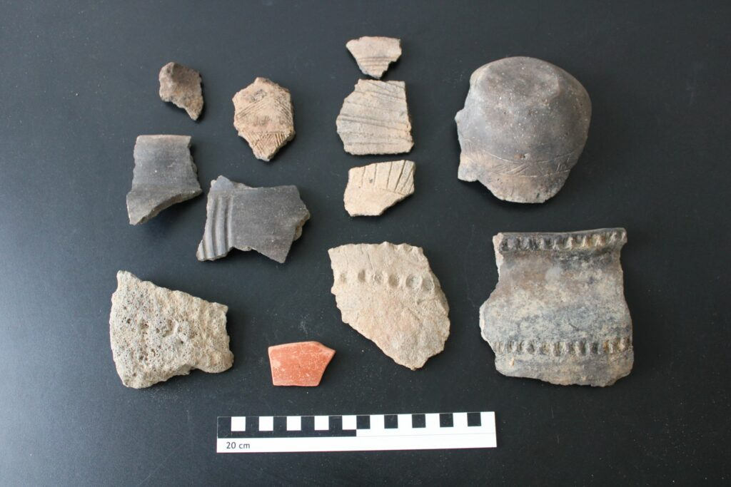 Auswahl von Funden aus einem Grubenhaus mit verzierter einheimischer Keramik, Terra Sigillata und Handmühlenfragment.