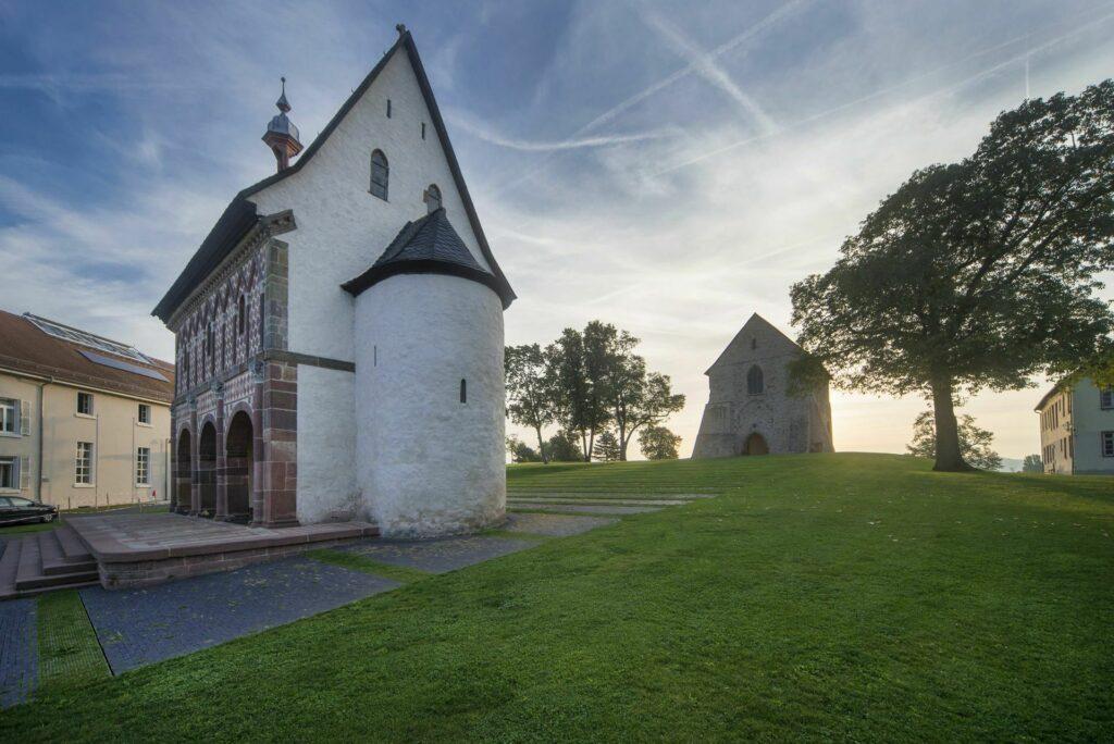 Die beiden ältesten Gebäude auf dem grünen Hügel: die karolingische Königshalle und das romanische Kirchenfragment.