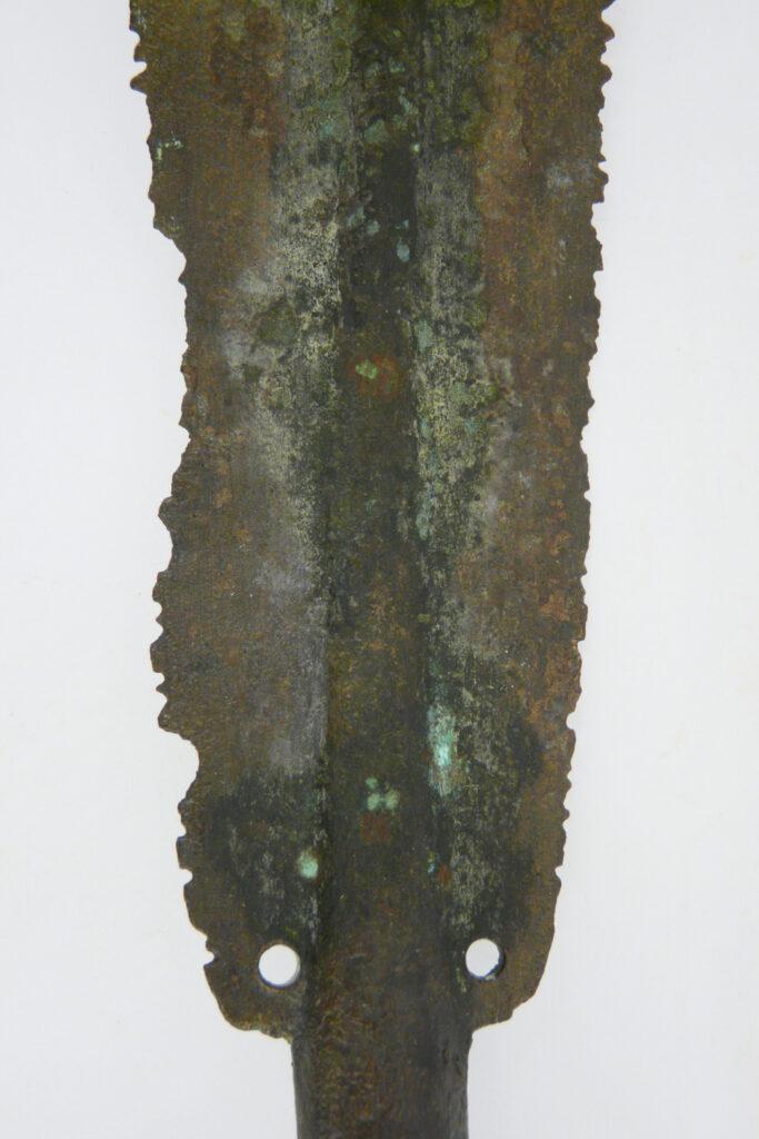 Blatt einer bronzenen Lanzenspitze mit absichtlich zerstörten Schneiden. Das Stück gelangte aus Sizilien nach Olympia.