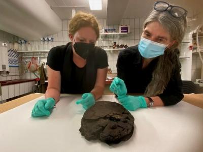 Lisa Renn (links) und Doris Mührenberg (rechts) inspizieren den beim Luftangriff 1942 verschütteten Fund. Im Vordergrund sind die Verzierungen aus Zucker gut zu erkennen am hinteren Ende ist die Torte immer noch in Wachspapier eingeschlagen.