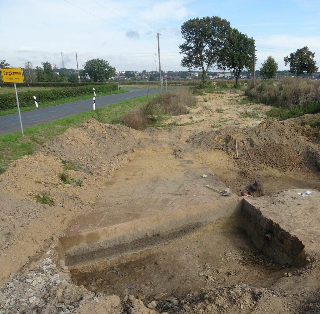 Direkt an der Stadtgrenze von Bergkamen liegt die Untersuchungsfläche, im Vordergrund ist eine Schnitt durch eine besonders große Grube zu sehen, auf deren Sohle eine mit Holzkohle angereicherte Schicht eingelagert ist.